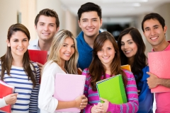 Happy group of college students smiling and holding notebooks